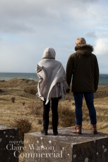couple standing on a concrete pillar at Gullane