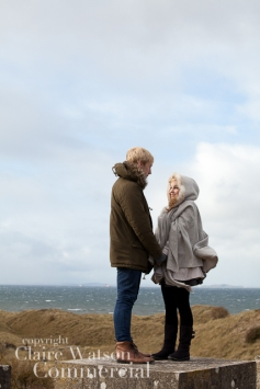 couple looking at each with sea behind