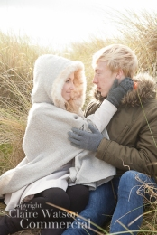 back lit couple sitting in long dune grass